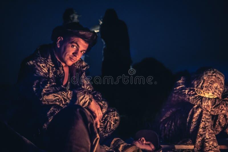 O pai e o filho que sentam-se pela fogueira no ar livre acampam na noite após o dia longo da caça imagens de stock