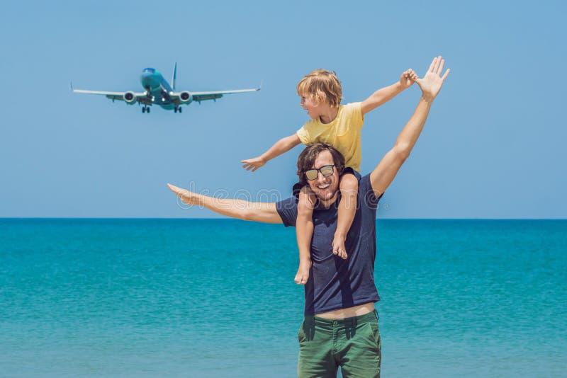 O pai e o filho têm o divertimento na praia que olham os planos de aterrissagem Viagem em um avião com conceito das crianças fotografia de stock