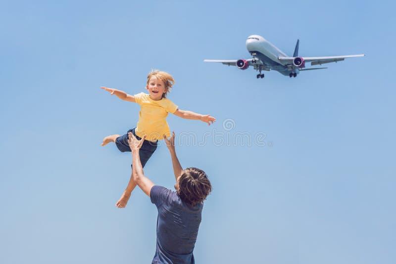 O pai e o filho têm o divertimento na praia que olham os planos de aterrissagem Viagem em um avião com conceito das crianças foto de stock