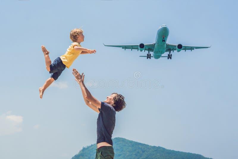 O pai e o filho têm o divertimento na praia que olham os planos de aterrissagem Viagem em um avião com conceito das crianças foto de stock royalty free