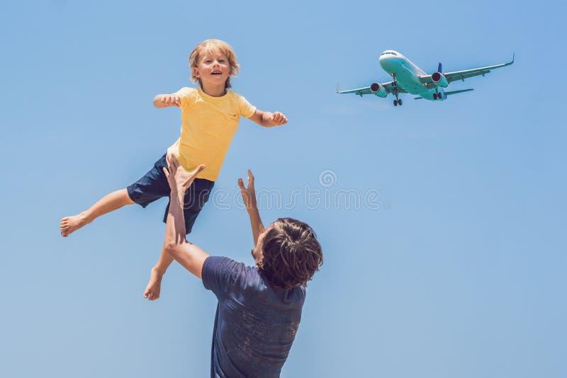 O pai e o filho têm o divertimento na praia que olham os planos de aterrissagem Viagem em um avião com conceito das crianças fotos de stock