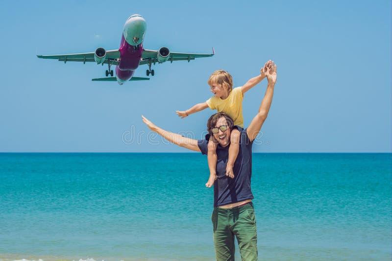 O pai e o filho têm o divertimento na praia que olham os planos de aterrissagem Viagem em um avião com conceito das crianças imagem de stock