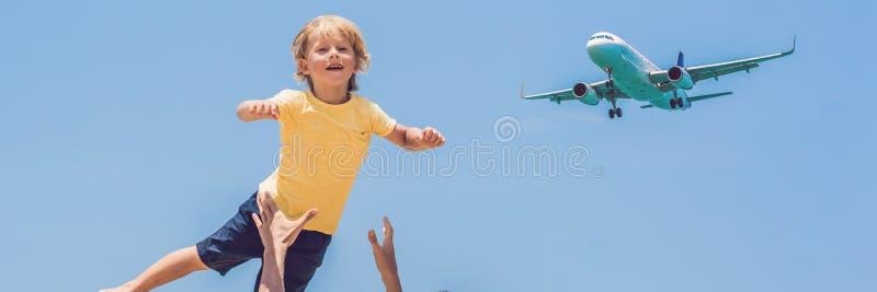 O pai e o filho têm o divertimento na praia que olham os planos de aterrissagem Viajando em um avião com a BANDEIRA do conceito d imagens de stock royalty free