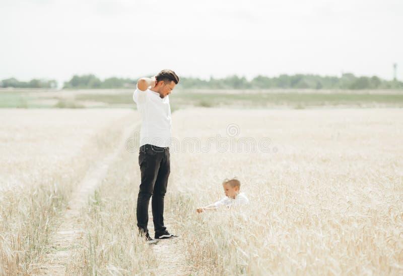 O pai e o filho têm um resto no campo de trigo no tempo do dia Povos que relaxam fora foto de stock royalty free