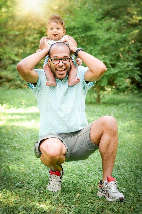 O pai e o filho estão jogando junto em um parque Únicos felizes descascam foto de stock