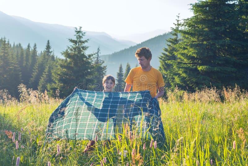 O pai e o filho estão jogando no prado alpino fotos de stock royalty free