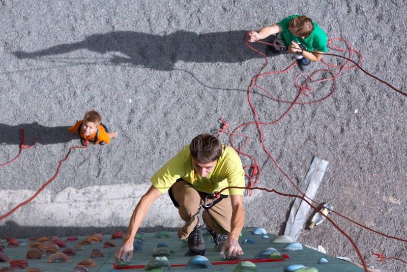 O pai e o filho executam a raça de relé de escalada da velocidade foto de stock