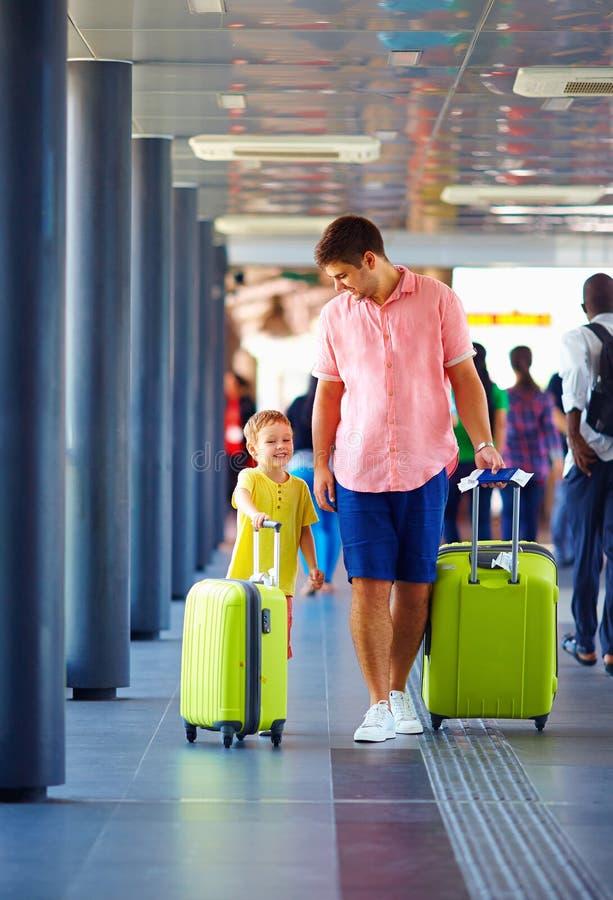 O pai e o filho felizes estão indo embarcando no avião, férias de verão fotografia de stock