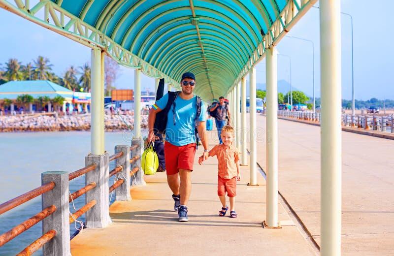 O pai e o filho felizes estão indo embarcar um navio na estação do cais foto de stock