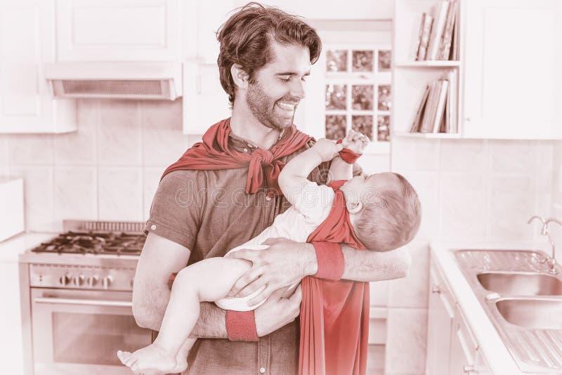 O pai e o filho no super-herói trajam o jogo na cozinha ilustração royalty free