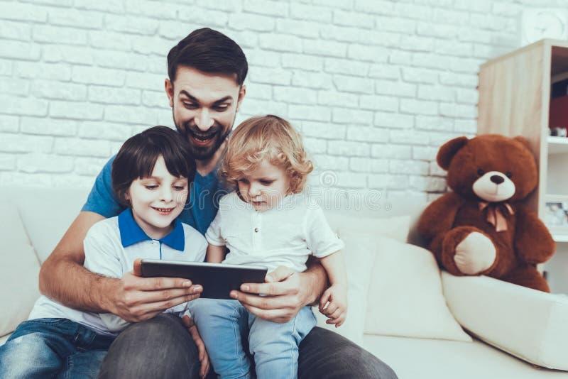 O pai e os filhos estão olhando um vídeo no PC da tabuleta imagem de stock royalty free