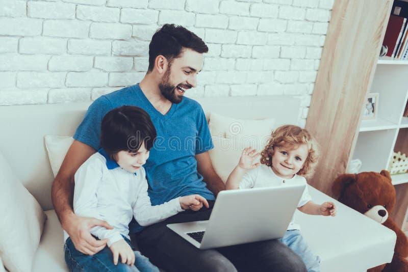 O pai e os filhos estão olhando um vídeo no portátil fotografia de stock