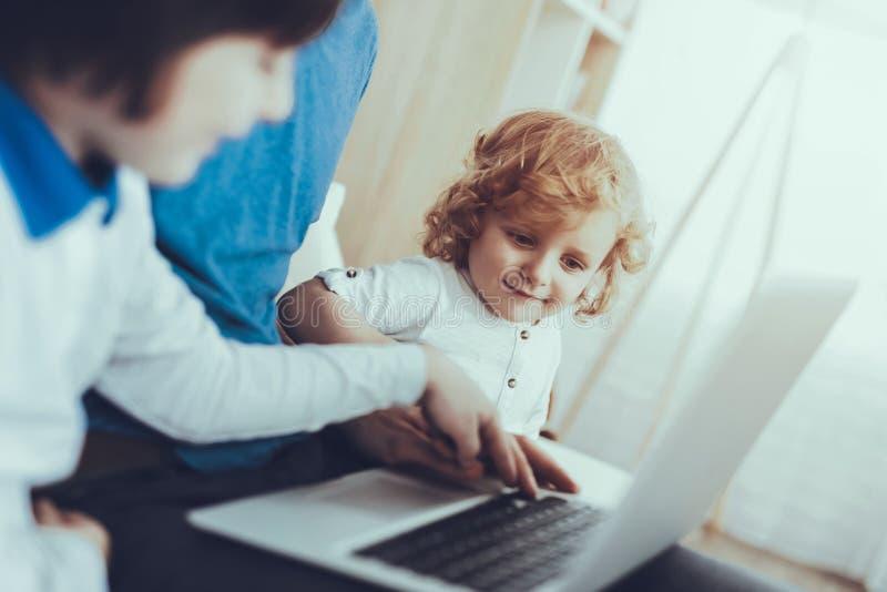 O pai e os filhos estão olhando um vídeo no portátil foto de stock royalty free