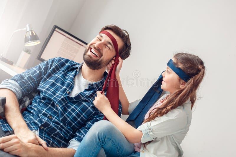 O pai e pouca filha em casa que sentam a menina apertam o laço na cabeça do pai alegre foto de stock royalty free