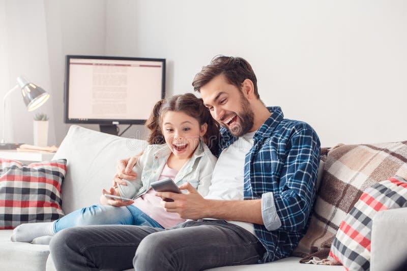 O pai e pouca filha em casa que sentam a nova aplicação da menina da exibição do homem surpreenderam imagem de stock