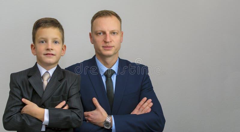 O pai e o sol com cruzamento armam-se no branco Estão dobrando seus braços sobre a caixa foto de stock