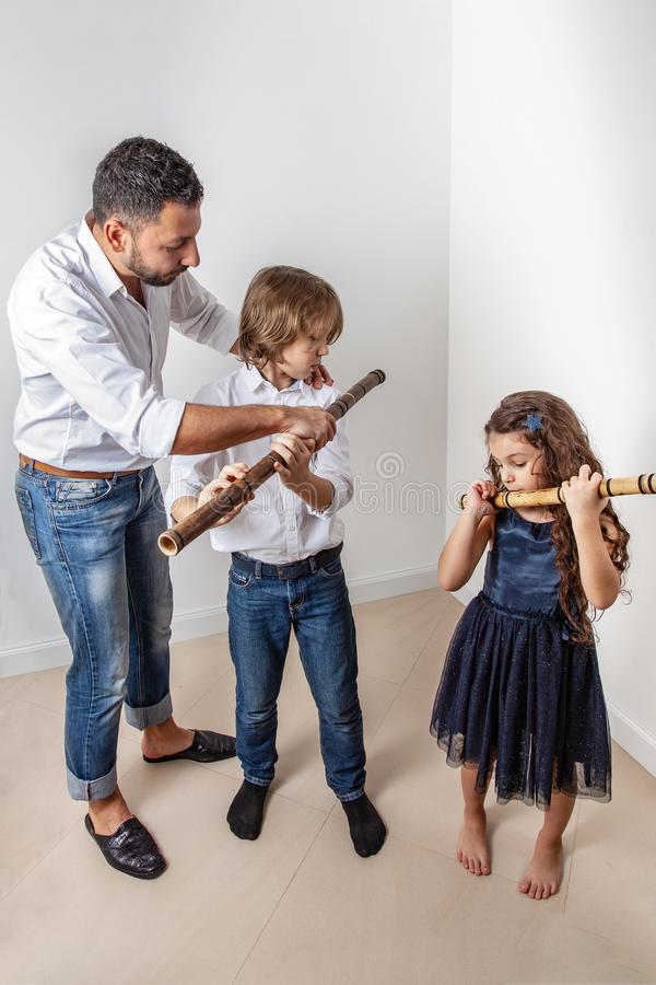 O pai ensina crianças jogar a flauta de bambu imagens de stock