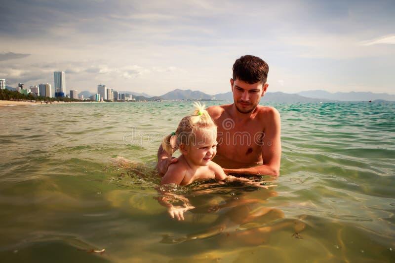 o pai ensina a filha pequena nadar na água do mar rasa fotos de stock royalty free