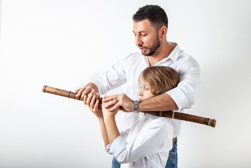 O pai ensina o filho jogar a flauta de bambu foto de stock royalty free