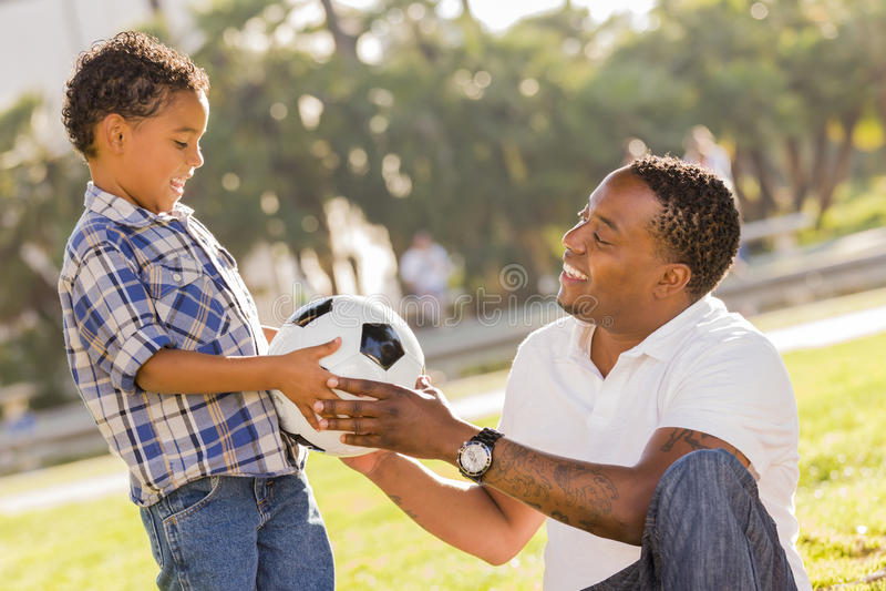 O pai entrega a esfera de futebol nova ao filho da raça misturada fotografia de stock