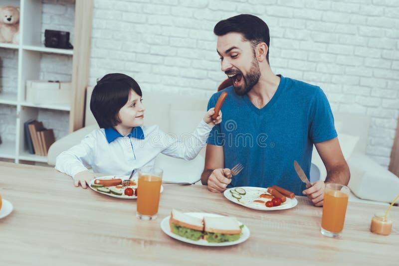 O pai está alimentando a um filho um café da manhã fotografia de stock