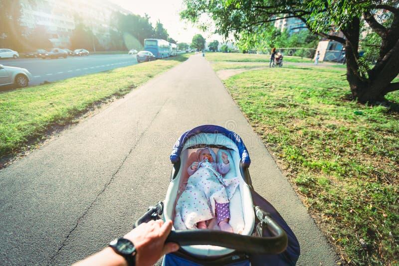 O pai está andando com seu bebê na rua na cidade A chupeta bonito do bebê do bebê encontra-se no transporte de bebê imagem de stock royalty free