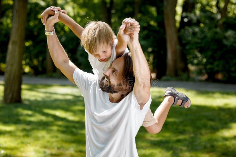 O pai está jogando com seu filho pequeno O pai aumentou seu pouco filho em seus ombro direito e sorriso O menino é surpreendido foto de stock