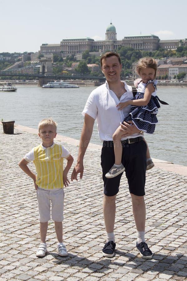 O pai feliz com duas crian?as est? nos bancos do Dan?bio fotos de stock royalty free