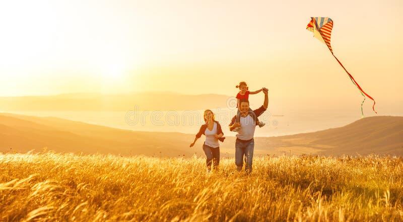 O pai feliz da família da filha da mãe e da criança lança um papagaio o fotos de stock