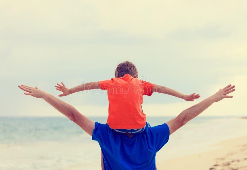 O pai feliz e o filho que jogam no mar encalham imagem de stock royalty free