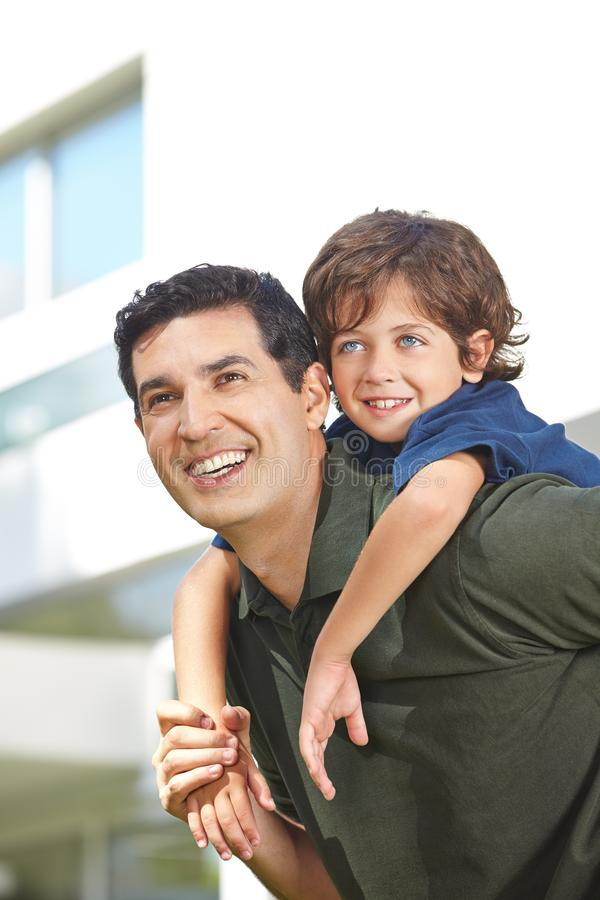 O pai feliz leva o filho na parte traseira foto de stock