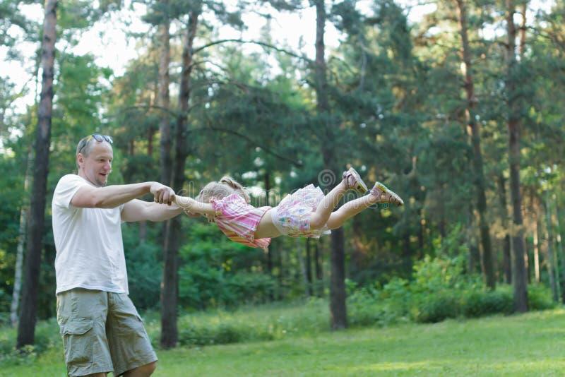 O pai feliz que gira ao redor sua filha no verão verde estaciona fora imagens de stock