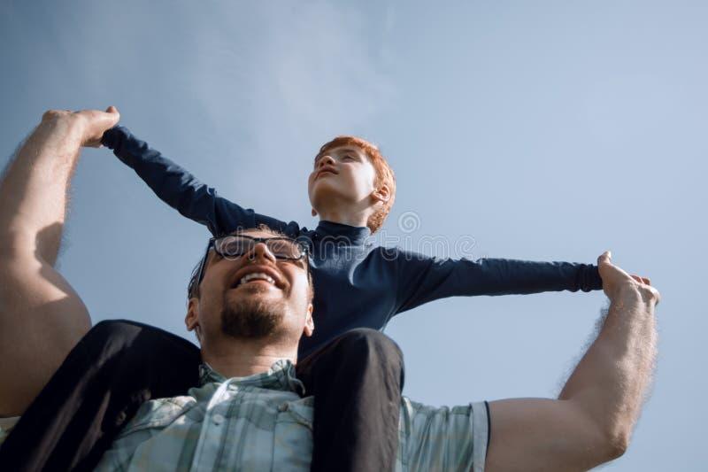 O pai feliz tem um filho pequeno em seus ombros imagens de stock