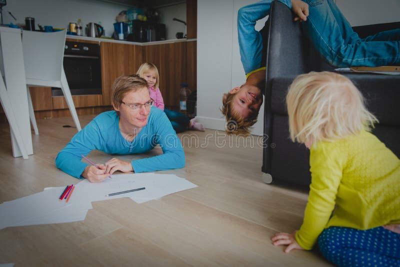 O pai fica a casa com filho e a filha, crianças tem o divertimento fotografia de stock