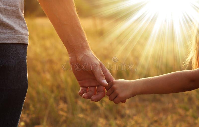 O pai guarda a mão de uma criança pequena fotos de stock royalty free
