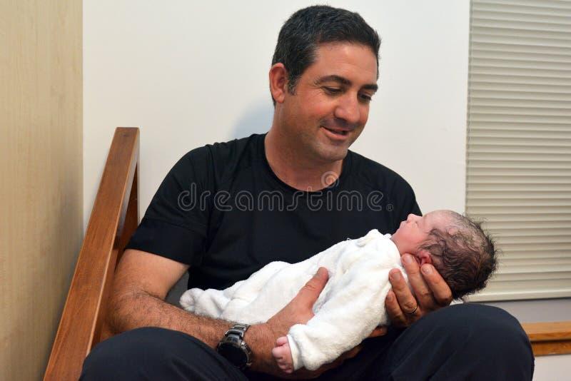O pai guarda seu bebê recém-nascido foto de stock