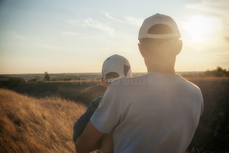 O pai guarda um filho em seus braços, no campo, eles olha o por do sol na distância, foto tonificada, amor, família imagem de stock