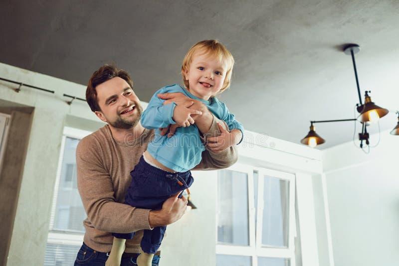 O pai joga com seu filho em um super-herói, um piloto no roo foto de stock