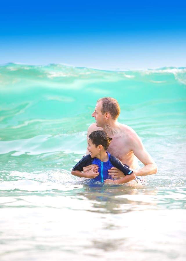 O pai levanta seu filho acima da onda grande fotografia de stock royalty free