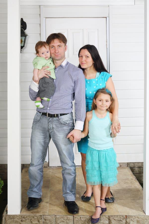 O pai, a mãe, o bebê e a filha estão no patamar da casa. fotos de stock royalty free