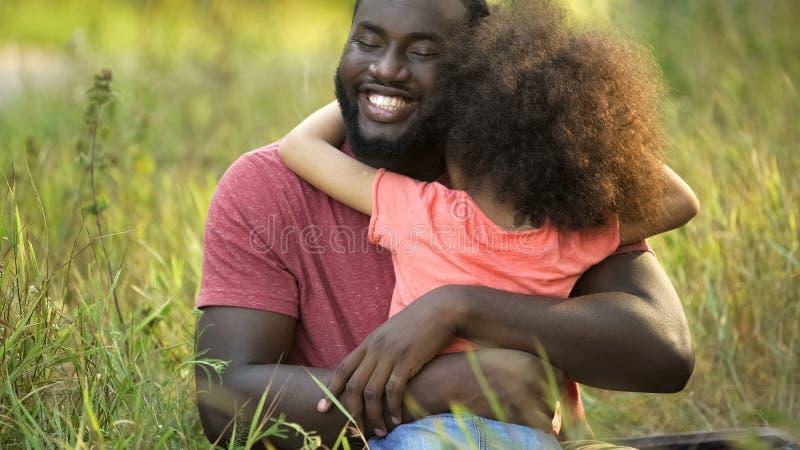 O pai o mais feliz no abraço apertado e macio amado de abraço da filha da terra dentro imagem de stock