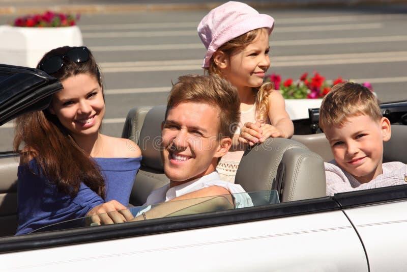O pai, a matriz e as crianças montam no carro imagem de stock