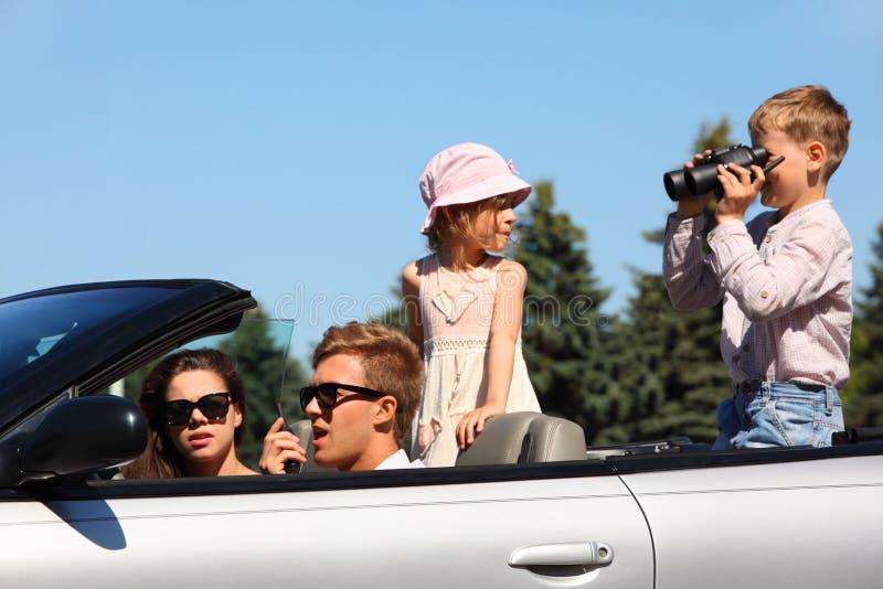 O pai, a matriz e duas crianças montam no carro foto de stock