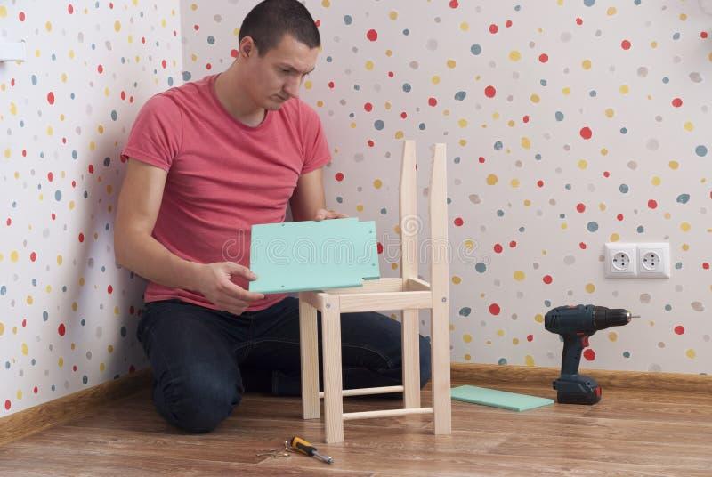 O pai monta uma cadeira para crianças fotos de stock royalty free