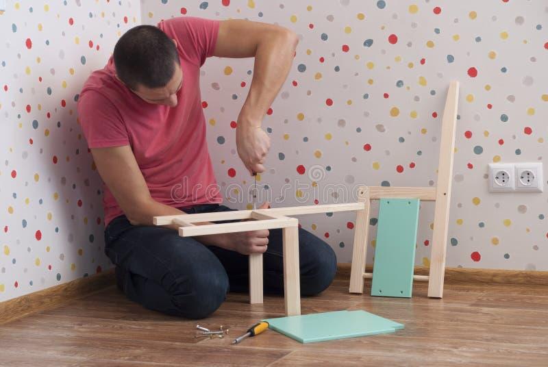 O pai monta uma cadeira para crianças imagens de stock royalty free