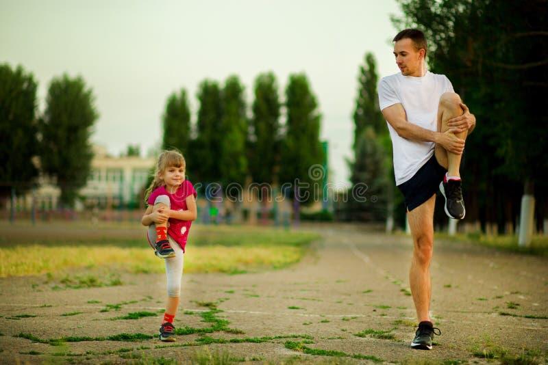 O pai novo atlético e a filha pequena fazem exercícios no estádio fotos de stock