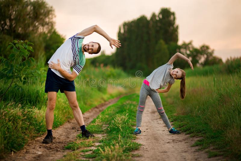 O pai novo atlético e pouca filha fazem exercícios Estilo de vida saud?vel foto de stock