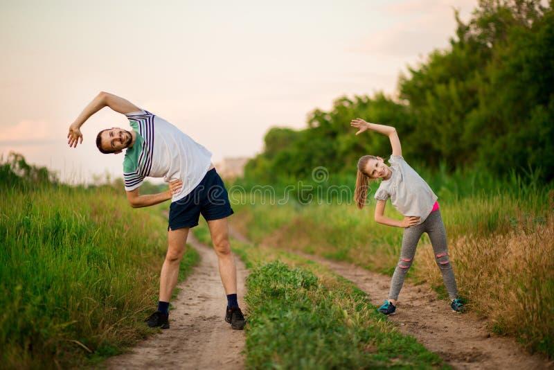 O pai novo atlético e pouca filha fazem exercícios Estilo de vida saud?vel fotos de stock