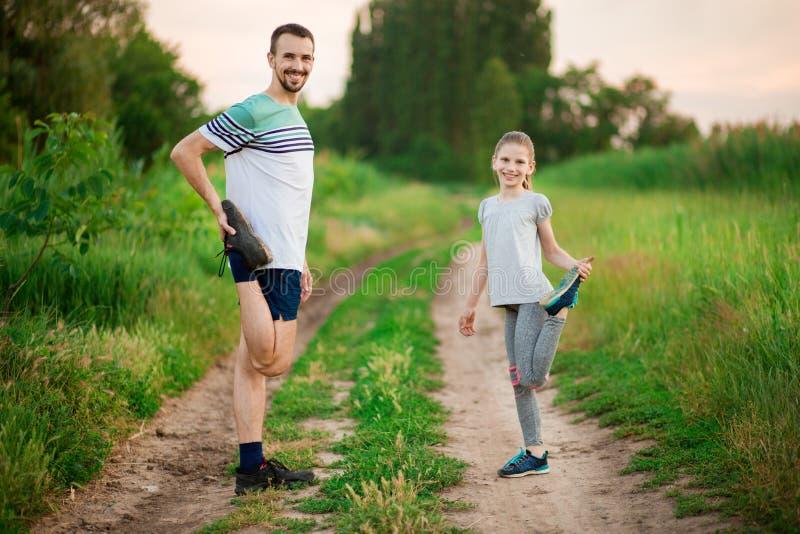 O pai novo atlético e pouca filha fazem exercícios Estilo de vida saud?vel imagens de stock royalty free