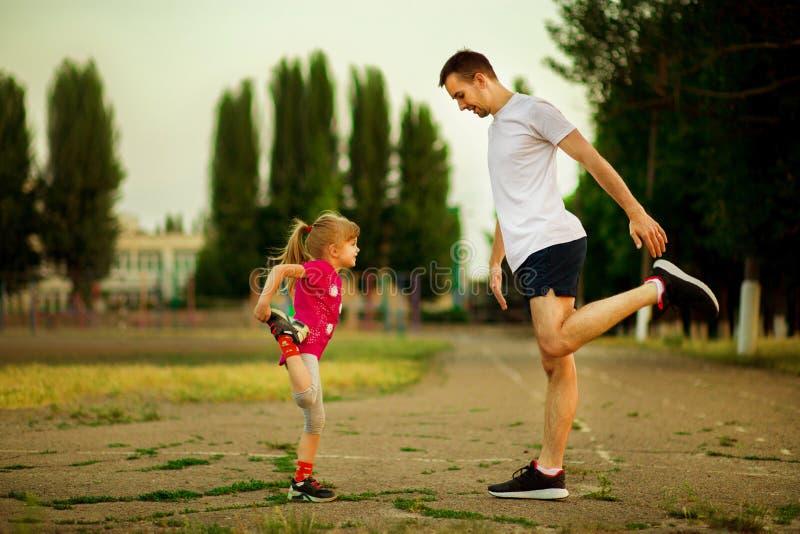 O pai novo atl?tico e a filha pequena fazem exerc?cios no est?dio fotos de stock royalty free